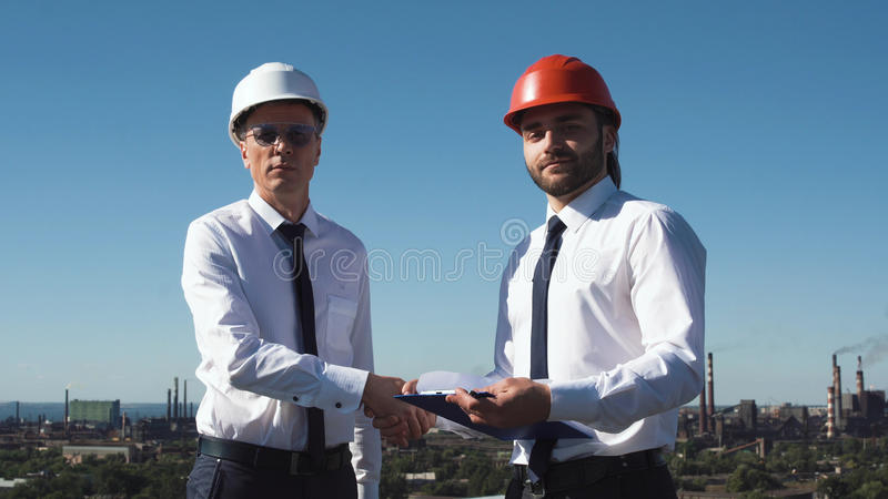 Two young male architects or engineers make deal stock photos