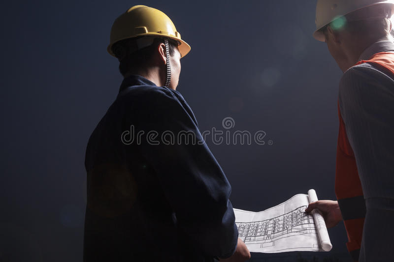 Two young male engineers in hardhats looking down at a blueprint at dusk, rear view royalty free stock image