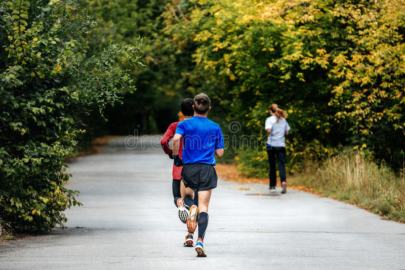 Two young men athletes runners run. A marathon in autumn city Park stock images