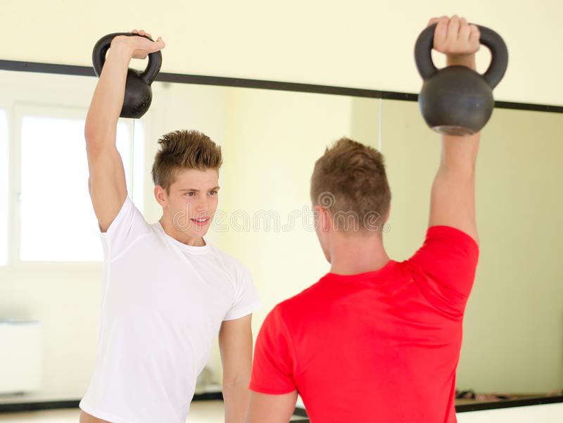 Two young men in gym working out with kettlebells stock images