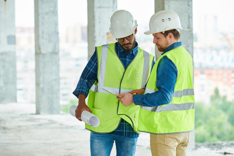 Construction engineers studying project on tablet stock images