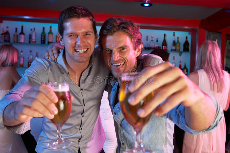 Two Young Men Having Fun In Busy Bar. Two Young Men Having Fun Drinking In Busy Bar stock images