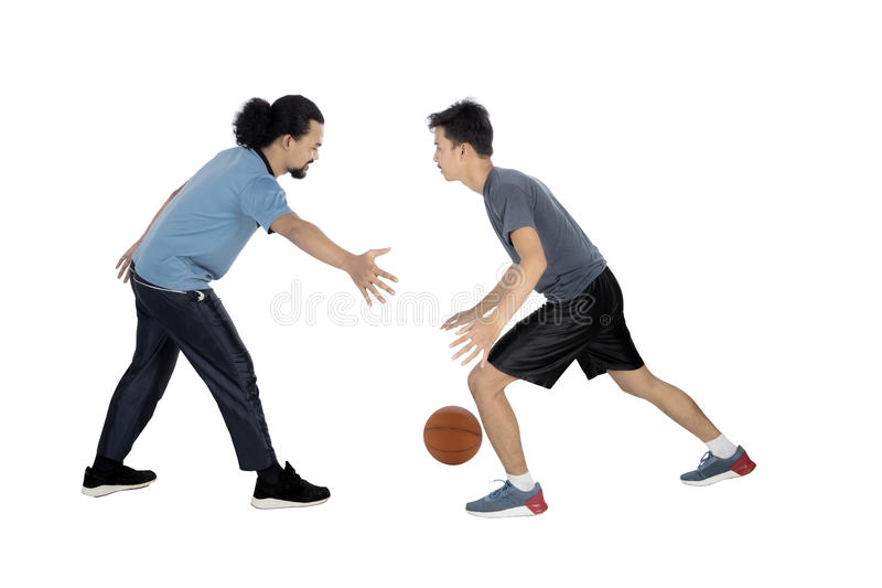Two young men playing basketball. Full length of two young multiracial men playing basketball in the studio, isolated on white background stock photos