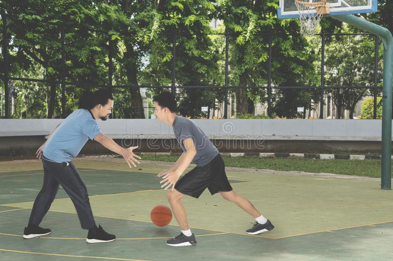 Two young men playing basketball at outdoors. Picture of two young men playing basketball together while doing a friendly match in the basketball field royalty free stock photo