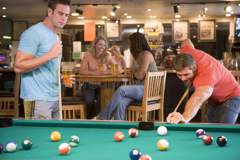 Two young men playing pool at a bar. With women in the background stock photo