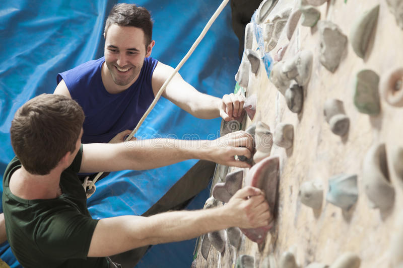 Two young men smiling at each other and climbing in an indoor climbing gym stock image