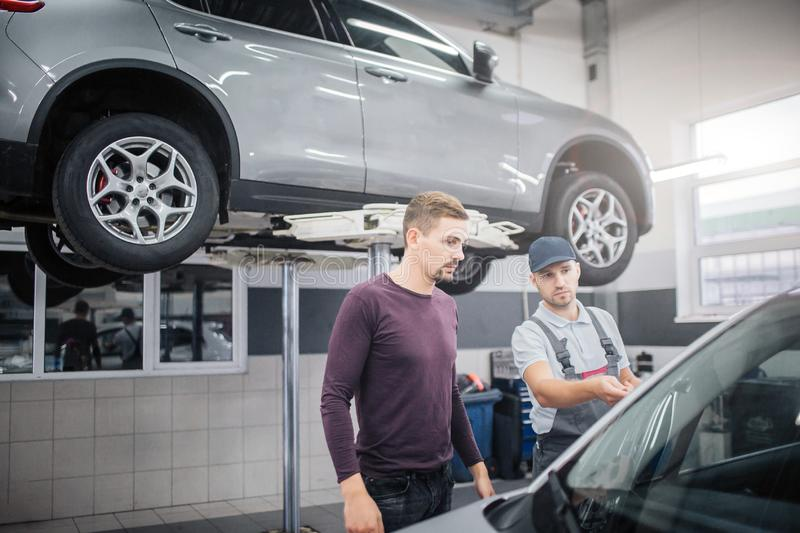 Two young men stand in garage at car. Worker points on automobile. Owner looks at it. They are serious and concentrated royalty free stock photography