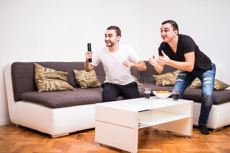 Two young men watching a football match on tv. Sport fans stock images