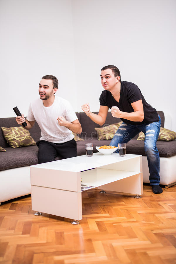 Two young men watching sports competition and drinking beer on tv. stock photos
