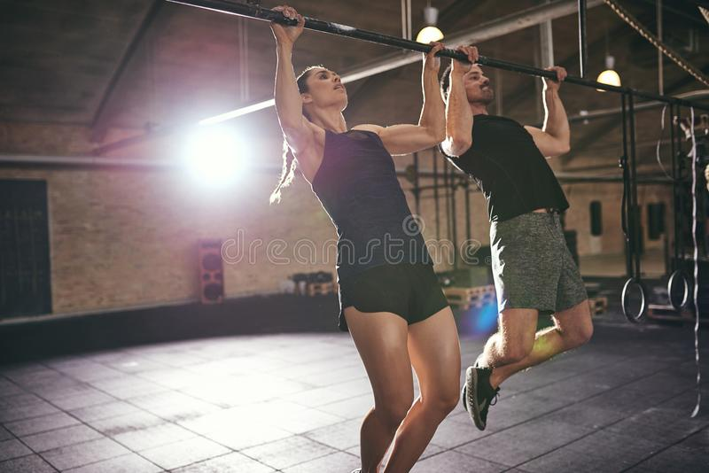 Young athletic sportspeople doing pull-ups in gym royalty free stock images