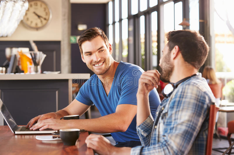 Two young men working on computers at a coffee shop stock photo