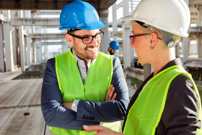 Two young modern architects or civil engineers talking about future project development on a construction site stock photos