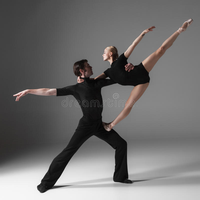 Two young modern ballet dancers on gray studio royalty free stock photos