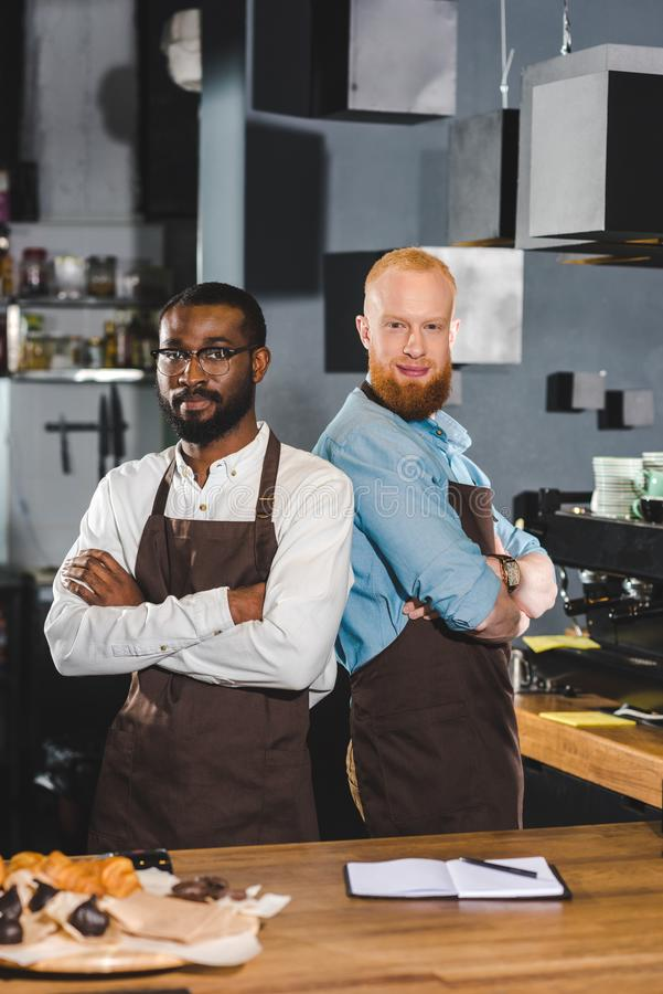 two young multicultural male baristas in aprons standing with crossed arms royalty free stock photo