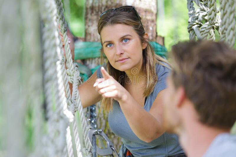 Two young people on adventure course rope bridge royalty free stock photography