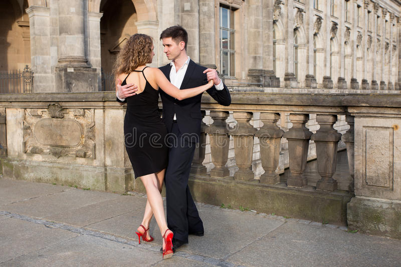 Two young people dancing tango outside on the old stone bridge stock photo