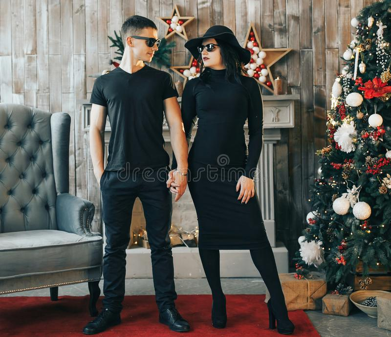 Two young people standing in front of a fireplace near Christmas tree royalty free stock photography
