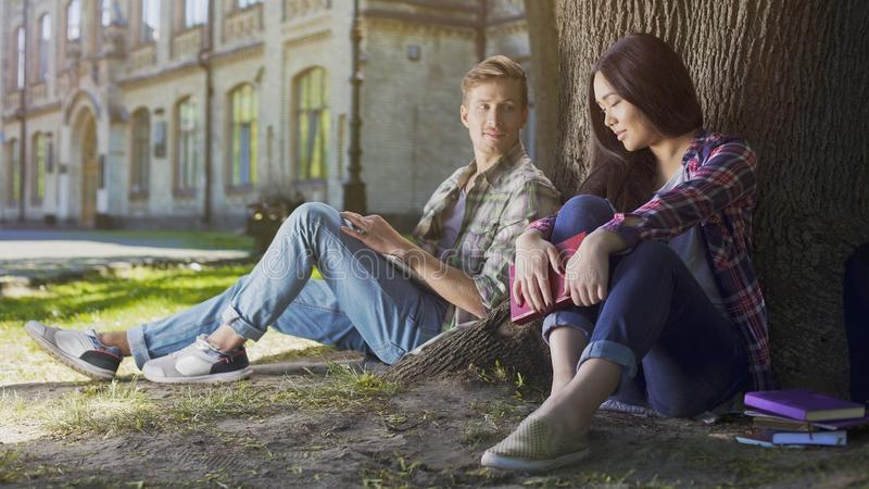 Two young people sitting under tree, girl looking down and guy looking at her royalty free stock images