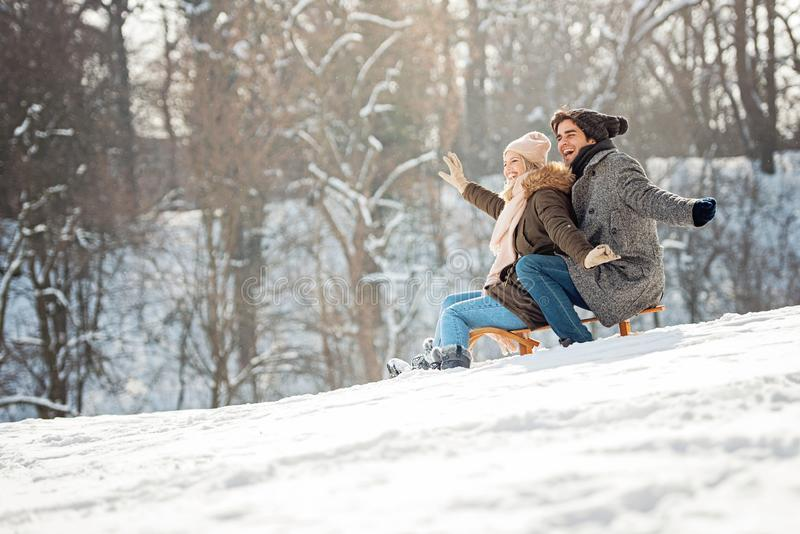 Two young people sliding on a sled. Having fun stock photography