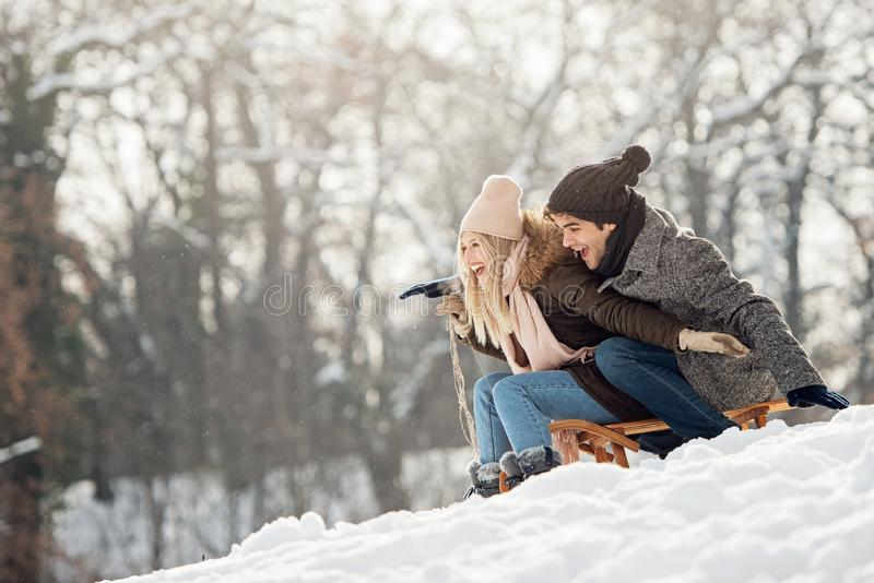 Two young people sliding on a sled stock photo