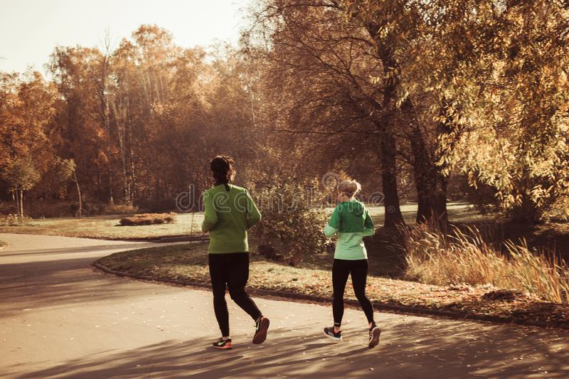 Two young people in sports suits are Jogging in the Park autumn warm Sunny weather, Moscow, Russia 18.10.2018 stock image