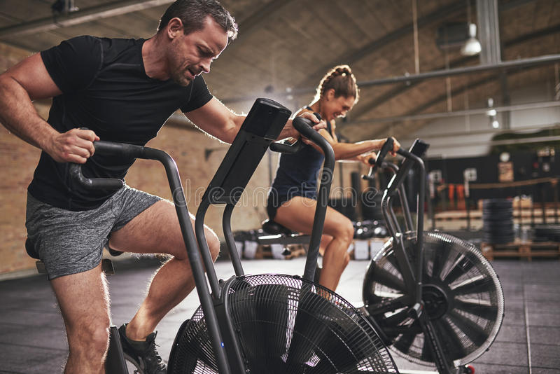 Two young people training toughly in simulators stock photos