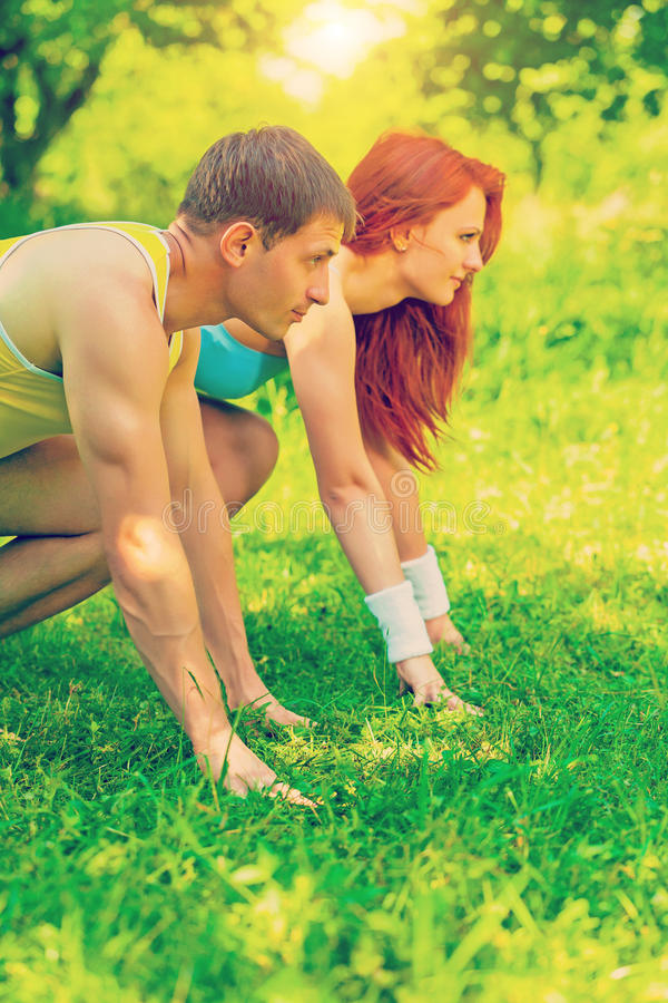 Two young people wearing sports clothes have low start on grass stock image