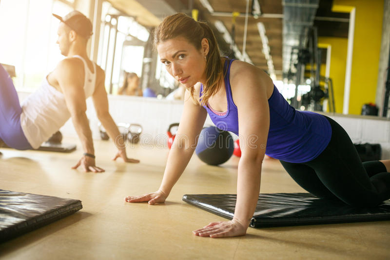 Two young people workout in healthy club. People doing push-ups. stock photos