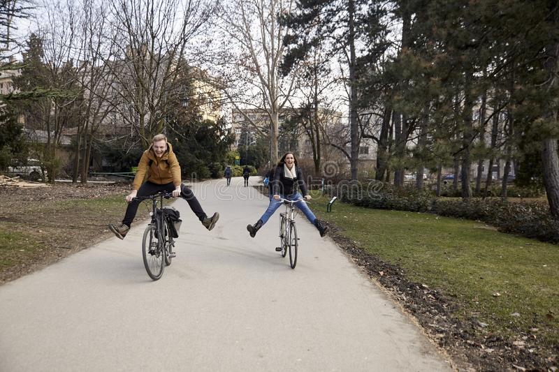 Two young people, 20-29 years old, riding a bicycle in a park with legs stretched, silly, laughing and having fun stock image