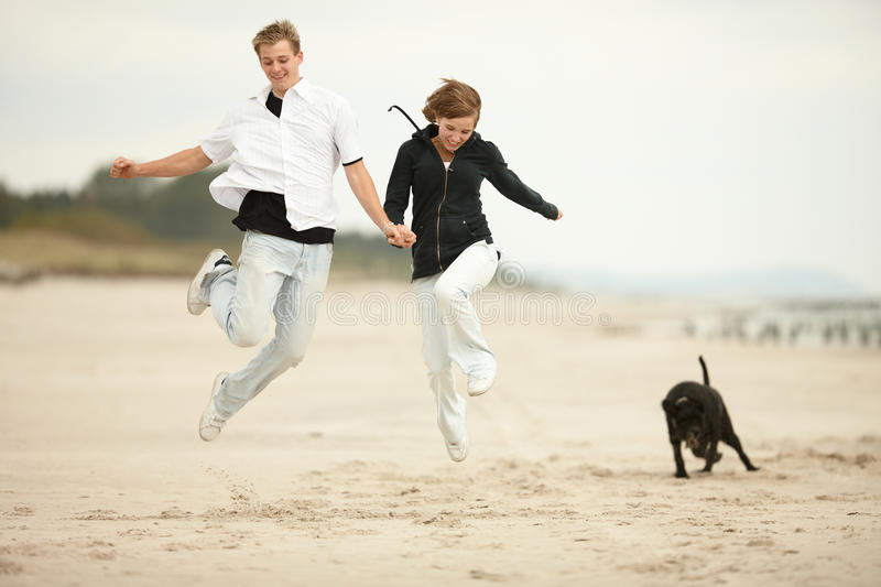 Two young poeple jumping on the beach and holding royalty free stock photography