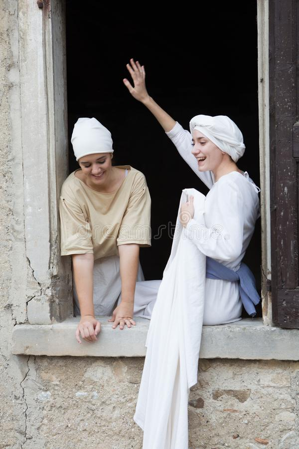 Pretty young actresses at the window in period costume, playing the role of common women attending the laundry royalty free stock photo
