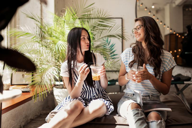 Two young pretty girls with long dark hair,wearing casual clothes, sit next to each other and drink coffee in a modern stock images