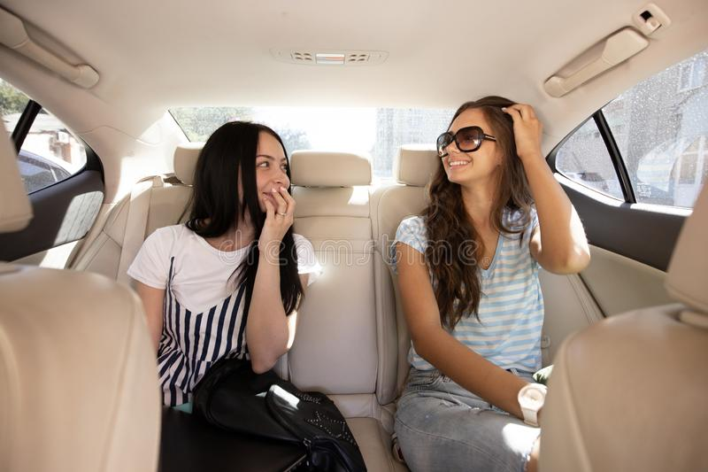 Two young pretty slim girls with long hair,dressed in casual style, are sitting in the back seat of a fancy and chatting stock photos