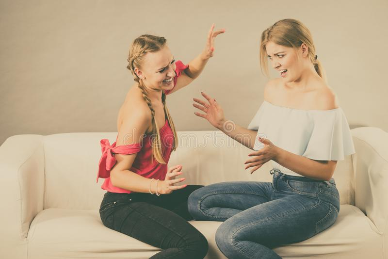 Two women having bad discussion. Two young pretty women being mad at each other after argue of fight. Friendship rivaly and envy problems royalty free stock photos