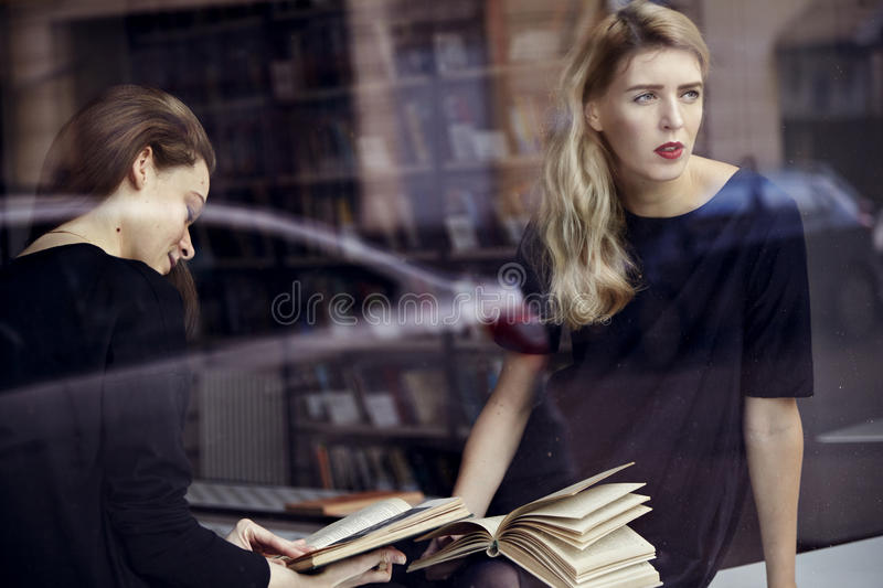 Two young professional women in a library reading books. Education concept.  stock photo