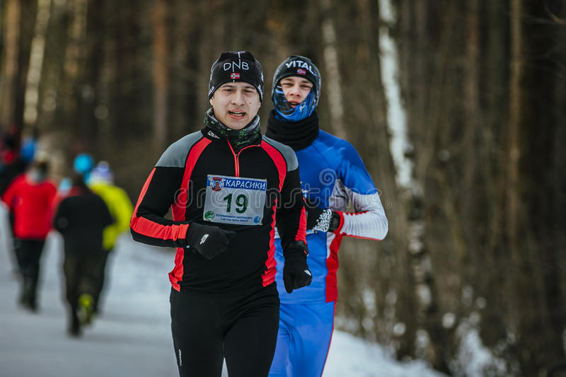 Two young runners competition. Ekaterinburg, Russia - November 14, 2015: two young runners, competition on snowy path Park during Urban winter marathon stock photos