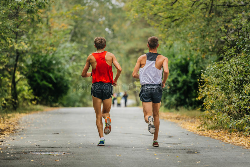 Two young runners synchronous running in autumn Park. Yellow leaves along road stock images