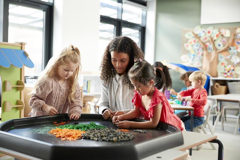 Two young schoolgirls standing at a table playing a game with their female teacher in an infant school classroom, selective focus royalty free stock photography