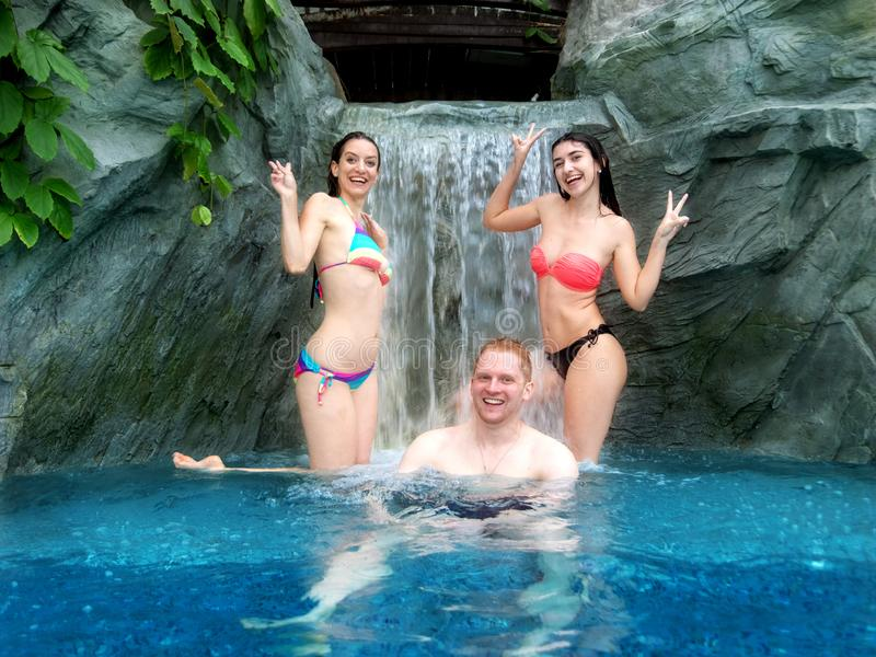 Two young sexy women in bikini and a man enjoying the falling water of the waterfall in the pool royalty free stock photo