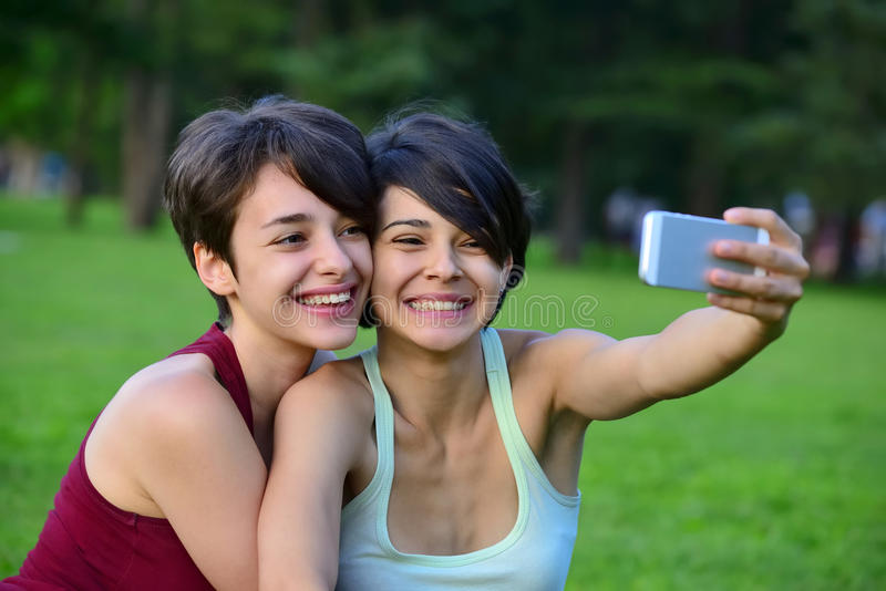 Two young short hair women taking photos with phone. Two young short hair women taking photos with phone in a park stock image