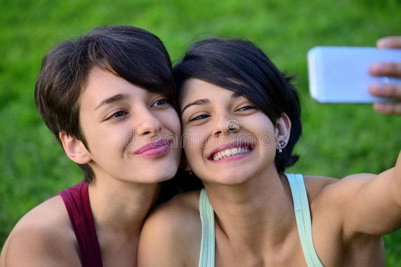 Two young short hair women taking photos with phone. Two young short hair women taking photos with phone in a park royalty free stock photos