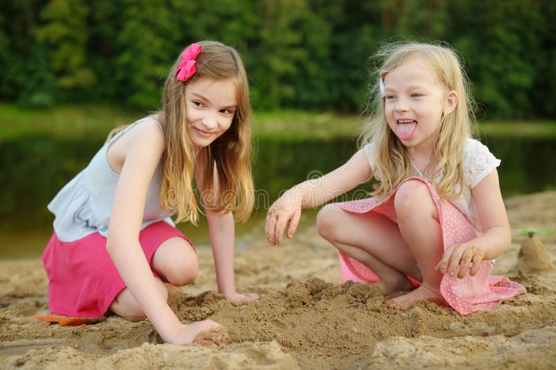 Two young sisters having fun on a sandy lake beach on warm and sunny summer day. Kids playing by the river royalty free stock images