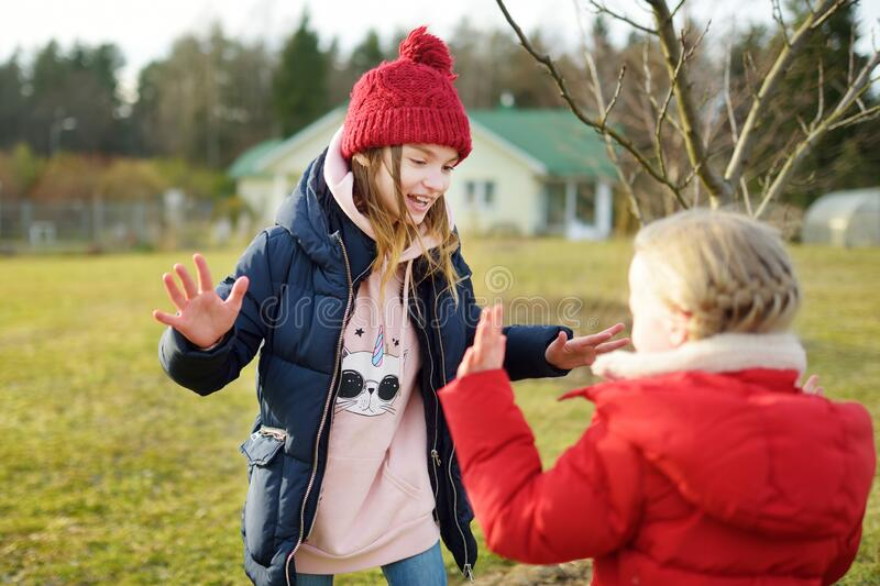 Two young sisters having fun together on beautiful spring day. Active family leisure with kids. Family fun outdoors stock photo