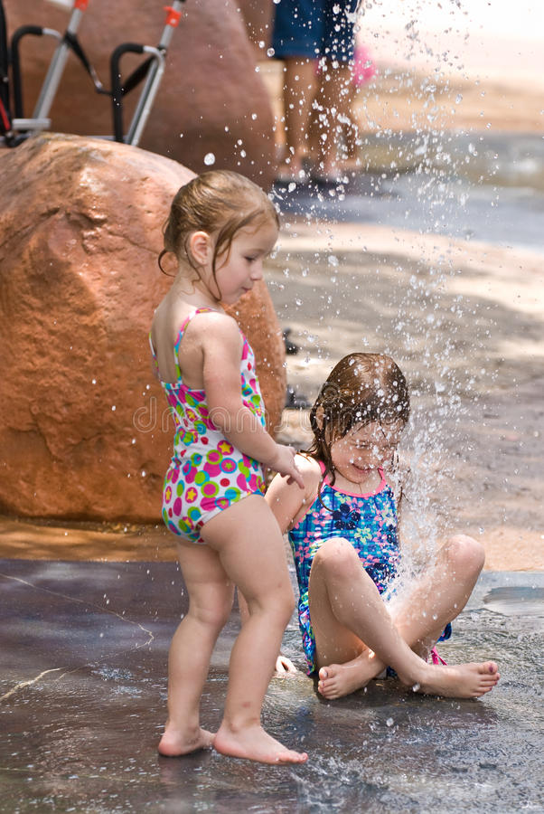 Two Young Sisters Playing In Water Together Stock Photo