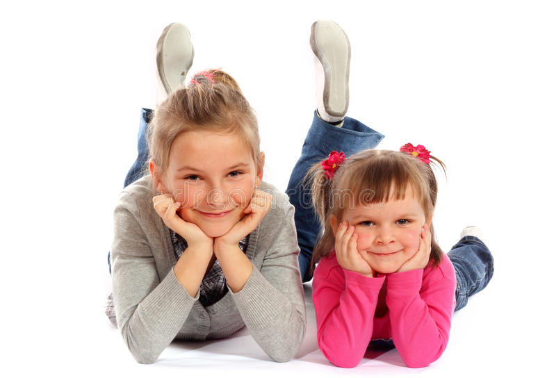 Two young sisters posing together in a studio stock photography