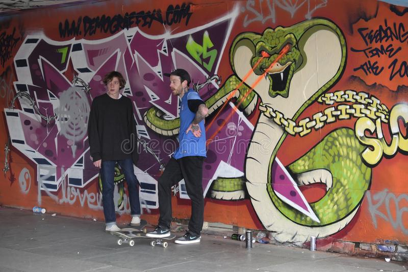 Two young skaters waiting their turn. Two skaters by a wall covered with graffiti, the Undercroft in the Southbank,London,uk stock image