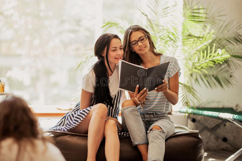 Two young slim girls with dark long hair,wearing casual outfit, look at a book in a modern coffee shop. royalty free stock photo