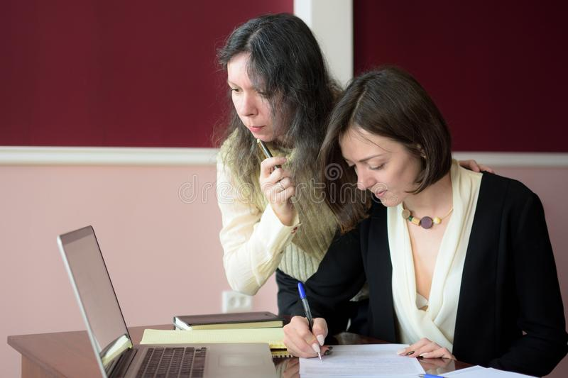 Two young smartly dressed women filling out forms at a vintage office desk in front of a laptop royalty free stock photography