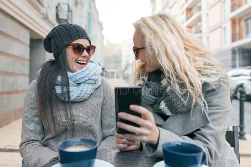 Two young smiling fashionable women having fun in outdoor cafe. Urban background, women laughing looking at mobile phone royalty free stock images