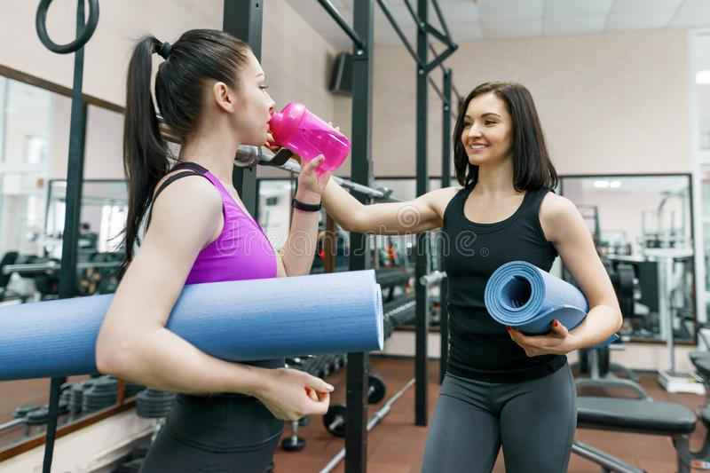 Two young smiling fitness women talking with sport mats in the gym. Training, teamwork, healthy lifestyle concept royalty free stock image